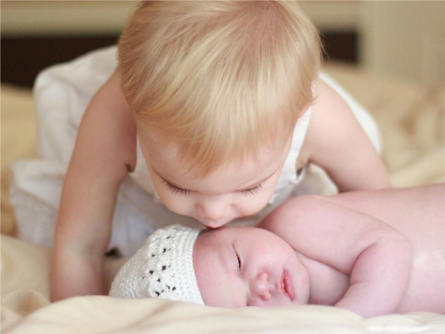 big sister gives newborn baby sister a kiss on the cheek