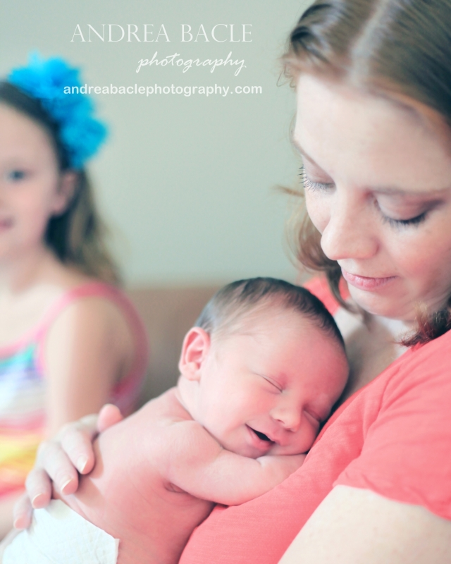 mom holding newborn baby with big sister at home